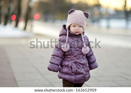 Little toddler girl having fun on winter day in a city