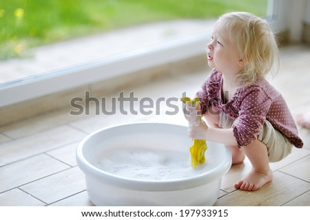Little toddler girl helping her mom to clean up - stock photo
