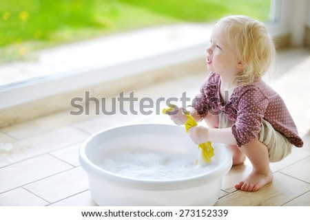 Little toddler girl helping her mom to clean up on spring day - stock photo