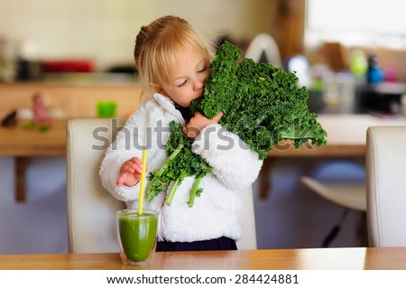 Little toddler girl in a white fluffy jacket holds a bunch of fresh kale and is about to drink a green smoothie in the kitchen