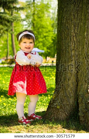 Little toddler girl laughing near the tree - stock photo