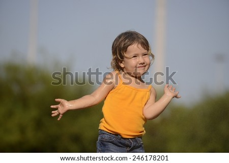 little toddler girl playing and posing in the summer rain - stock photo