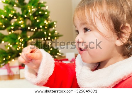 Little toddler girl playing in front of the Christmas tree - stock photo