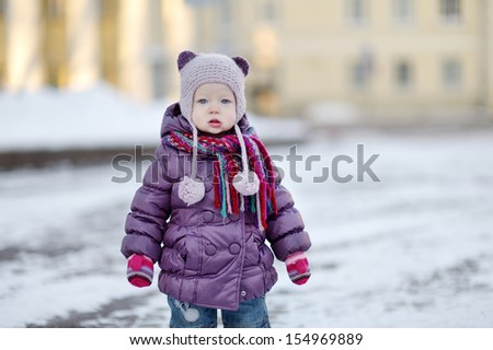 Little toddler girl portrait on winter day in city