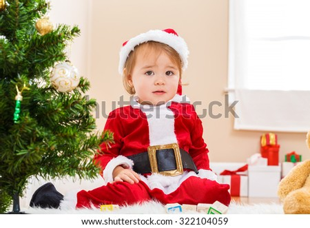 Little toddler girl sitting by the Christmas tree with a santa costume - stock photo