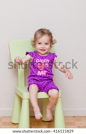 Little toddler girl sitting on her first own child chair. Happy baby feeling herself a little bit grown up. - stock photo