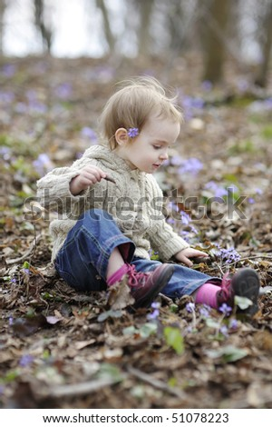 Little toddler girl touching first flowers of spring - stock photo