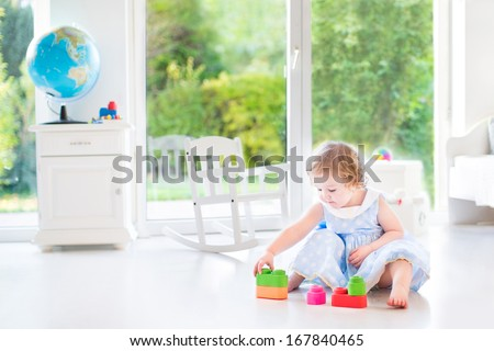 Little toddler girl with curly hair wearing a blue dress playing in a white sunny bedroom with a big window with garden view  - stock photo