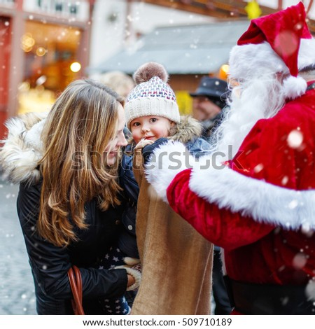 Little toddler girl with mother on Christmas market. Funny happy kid taking gift from bag of Santa Claus. holidays, christmas, childhood and people concept
