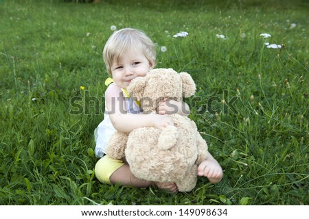 little toddler hugging her teddy bear, seated outdoors in the garden