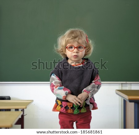 little toddler in a classroom in front of a chalkboard - stock photo