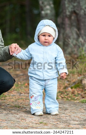 Little toddler in blue suit standing in the park, holding the hand of her mother - stock photo