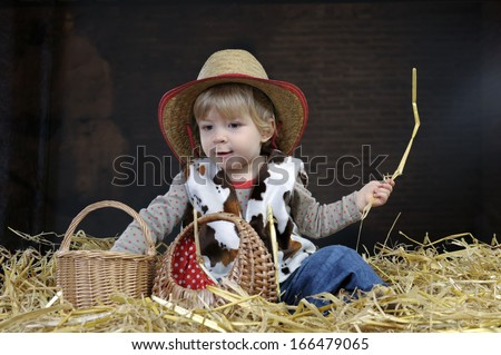 little toddler in cowboy outfit playing in a barn - stock photo