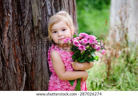 Little Toddler Lovely Girl With Flowers In Pink Dress At Beautiful Garden