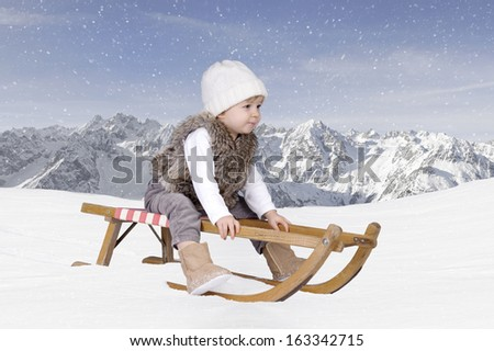 Little toddler outdoors in the snow in the mountains - stock photo