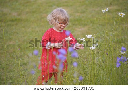 little toddler playing outdoors in the garden - stock photo