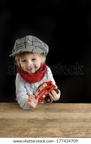 little toddler playing with wooden cars, on black background