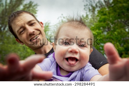 little toddler taking selfie with her daddy at a park in the summer with a shallow depth of field on daughter with bokeh - stock photo