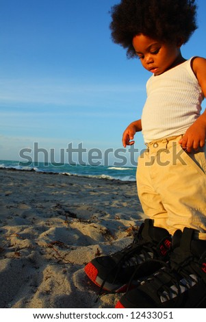 Little toddler wearing big shoes - stock photo