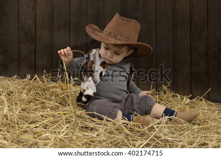 little toddler with cowboy hat in barn with straw - stock photo