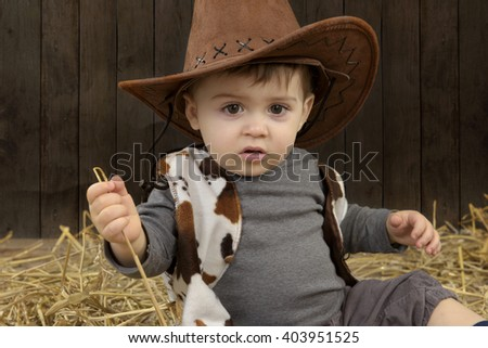 little toddler with cowboy hat in barn with straw