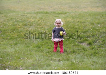little toddler with glasses playing in the garden