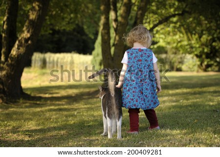 little toddler with her cat outdoors in the garden - stock photo