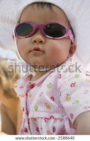 little todler wearing sunglasses and a hat - stock photo