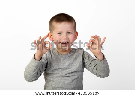 Little toothless boy with wide happy smile on face shows okey sign on gray background