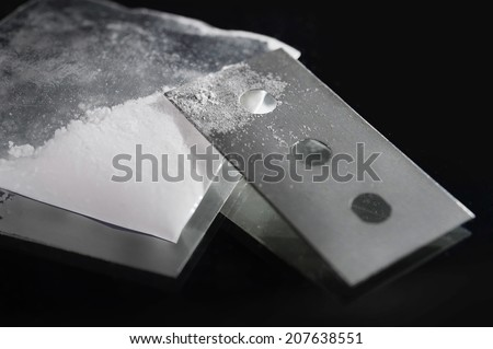 little transparent cocaine gram bag and drug stained razor blade on black background in drugs use and abuse and illegal substance addiction concept - stock photo