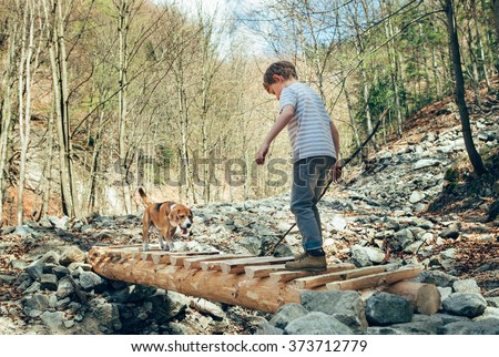 Little traveker in spring forest with his dog - stock photo