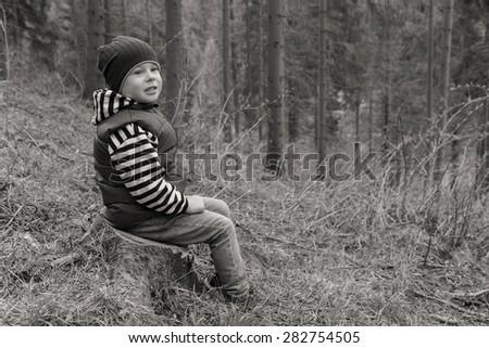 Little traveler. Little boy is resting in the forest. Travel, active children's recreation. - stock photo