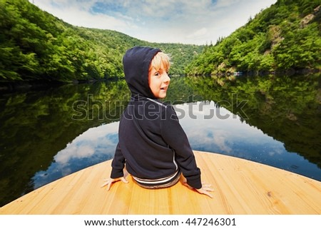 Little traveler on the river. Boy is sitting on the boat. - stock photo