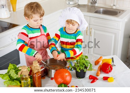 Little twins cooking italian soup and meal with fresh vegetables in home's white kitchen. Sibling children in colorful shirts.