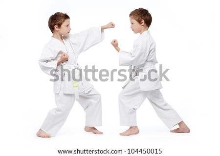 Little twins in uniform practicing judo, isolated on white - stock photo