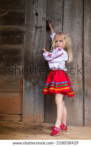 Little ukrainian girl in national traditional costume trying to open old wooden door - stock photo