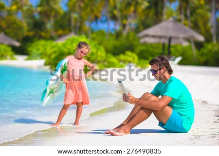 Little upset sad girl waiting father to swim while he working - stock photo