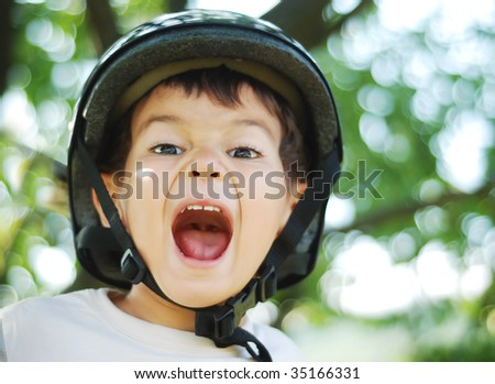 Little very cute kid with helmet on head and opened mouth - stock photo