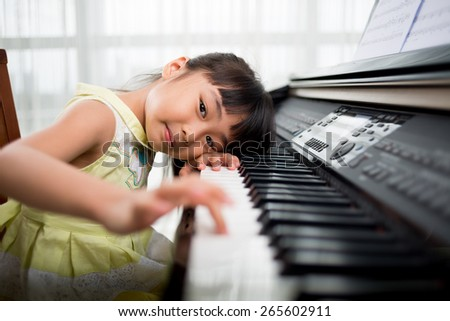 Little Vietnamese girl playing synthesizer and looking,at the camera buttons are digitally modified - stock photo