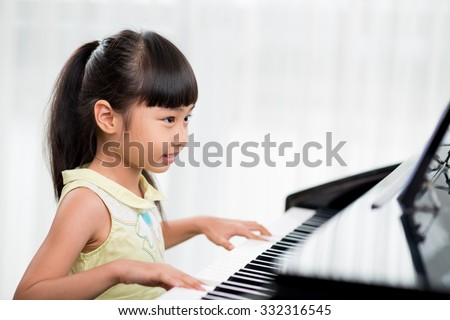 Little Vietnamese girl playing the piano at home - stock photo