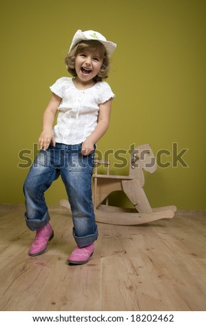 Little western girl and  rocking horse - stock photo