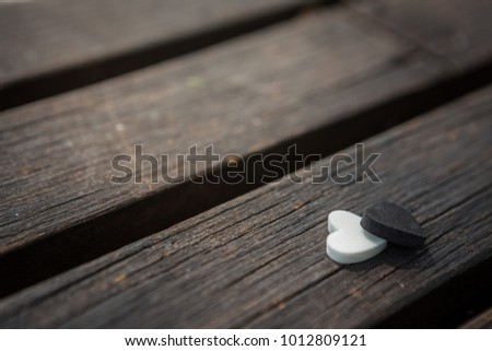 Little white and black heart on an old wooden table with sunlight background