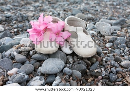 Little white boots with pink flowers on a stoned beach - stock photo