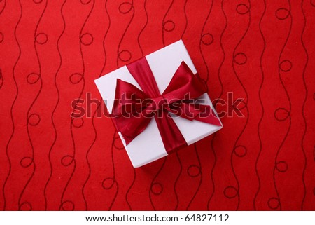Little white present with a red bow on red background