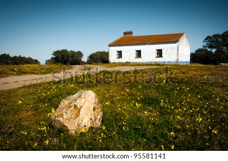 Little white rural house abandoned in the countryside with a rock in the foreground - stock photo