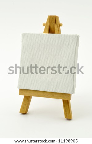 Little wood easel and white canvas - stock photo