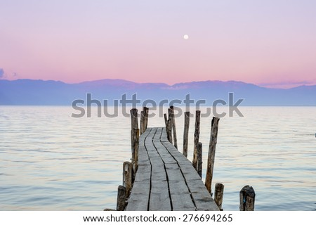 Little wooden boat dock with the pink sunset sky on the background in Lake Atitlan - the sun sets on the opposite site and the early moon is seen in the sky, Guatemala  - stock photo