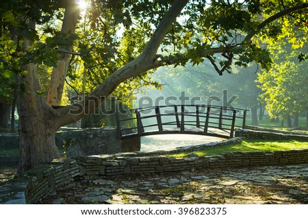 Little wooden bridge on first sunrays at morning in Topcider park - stock photo