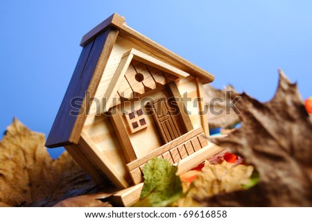 Little wooden house model under blue sky - stock photo