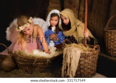Little 7 year old angel visiting a nativity scene reenacted - the baby is a doll - stock photo